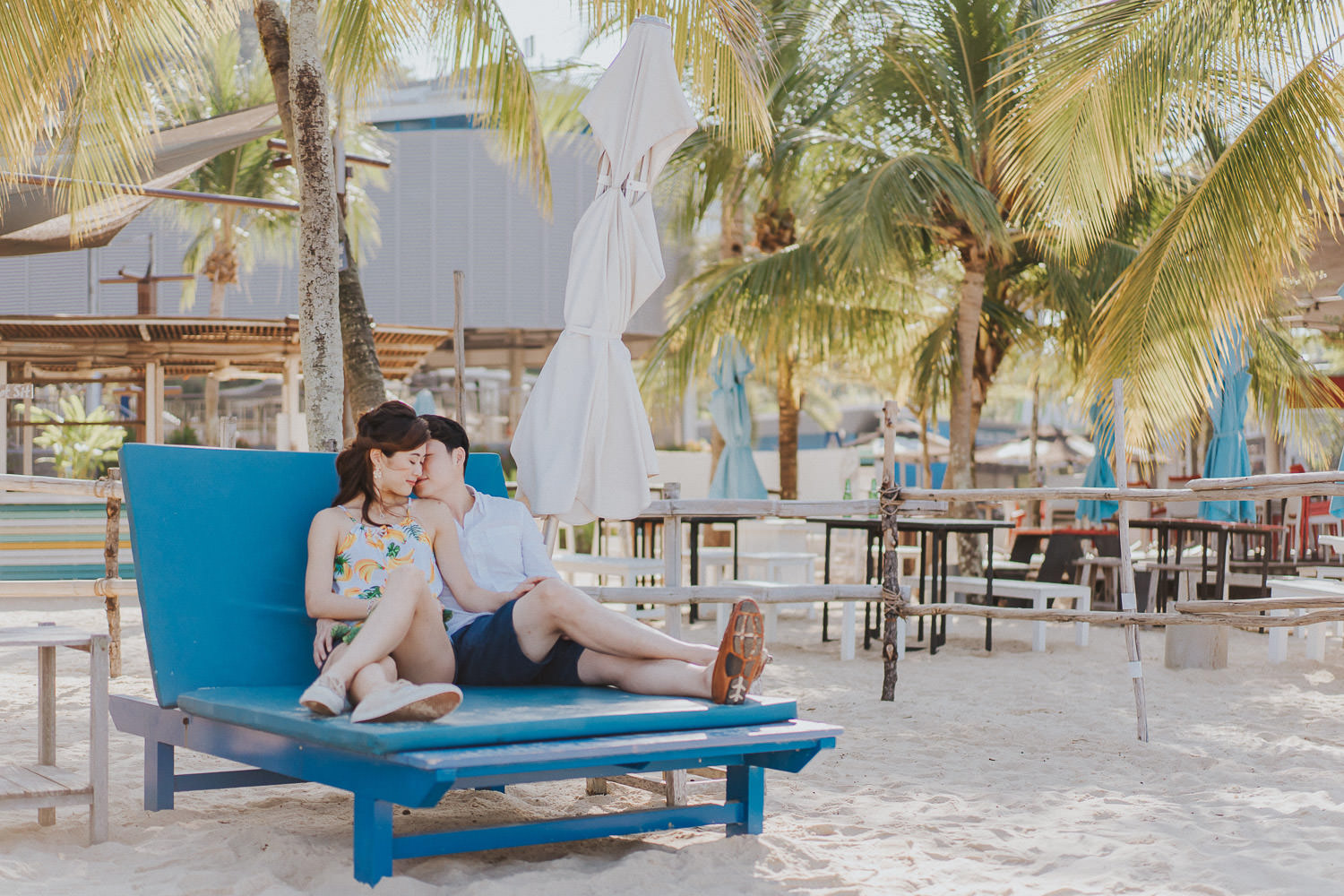 nicole and ping on a day bed at sentosa taking an engagement photo